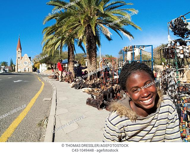Namibia - Vendor at the well-known open-air souvenir market in the centre of Namibia's capital Windhoek with the famous Christuskirche Church of Christ in the...