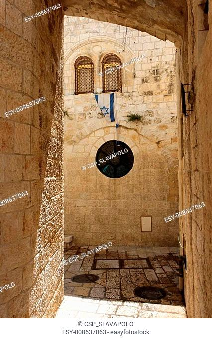 Arched passage in the Old City of Jerusalem with Israeli flag