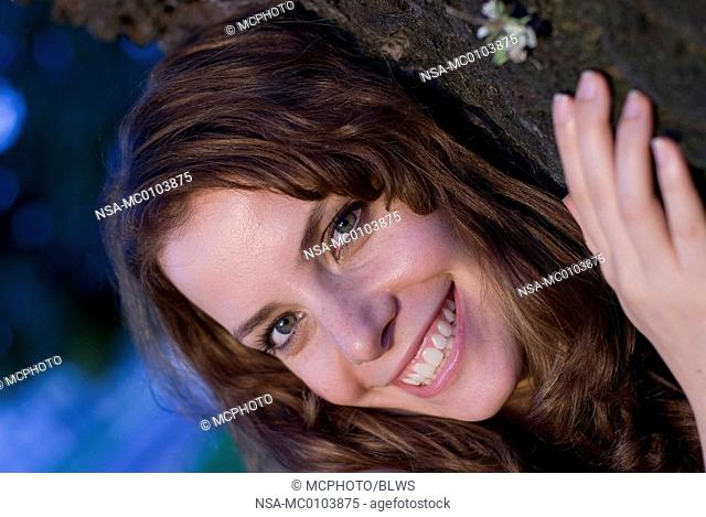 pretty woman with long brown hair snuggling into a tree