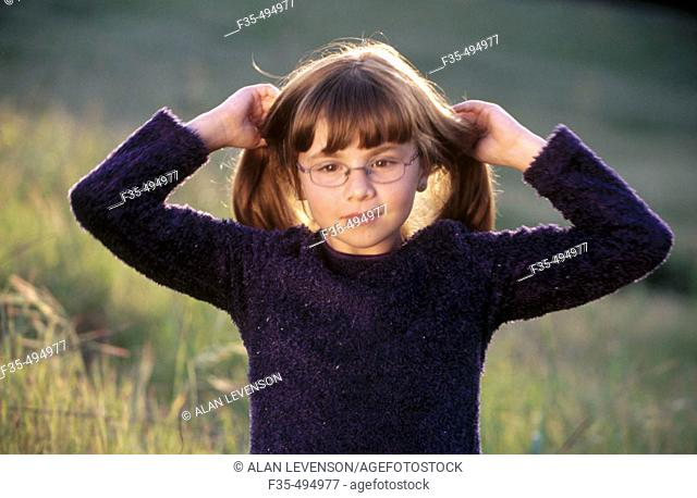 Intelligent girl with glasses fixing her hair