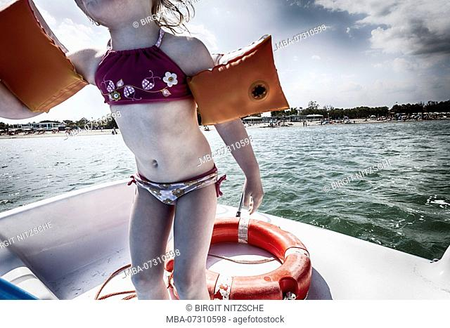 Little girl with water wings on boat