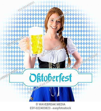 Composite image of oktoberfest girl smiling at camera holding beer