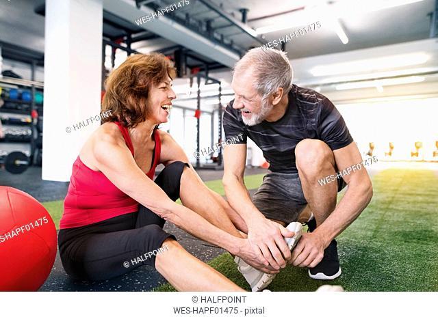 Happy senior couple exercising in gym