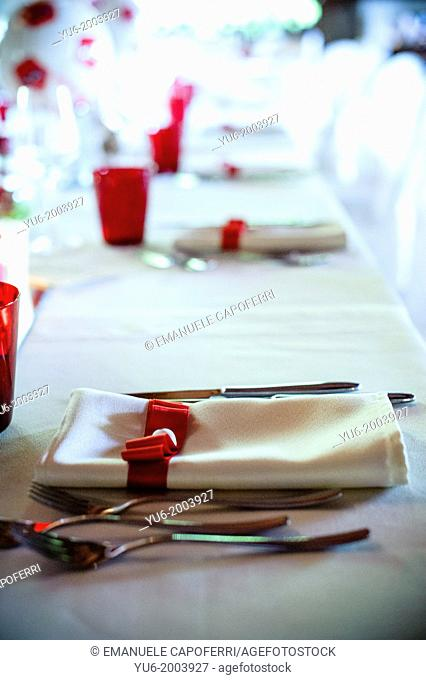 Cutlery and napkin noodle and ceramic heart above table set for wedding