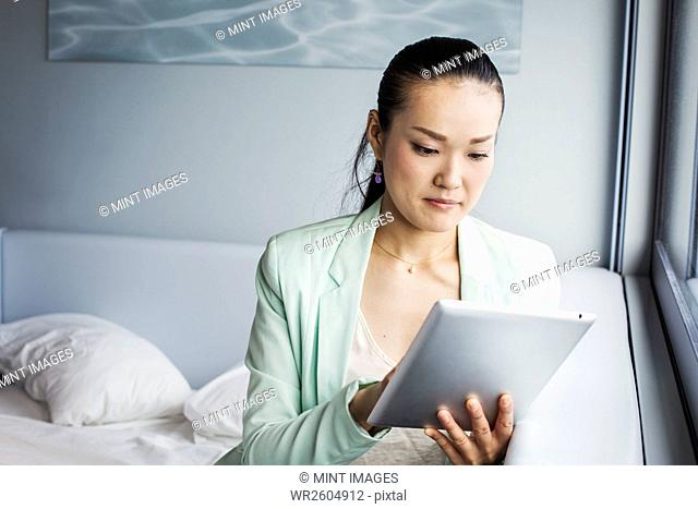 A business woman preparing for work, sitting on a bed using a digital tablet