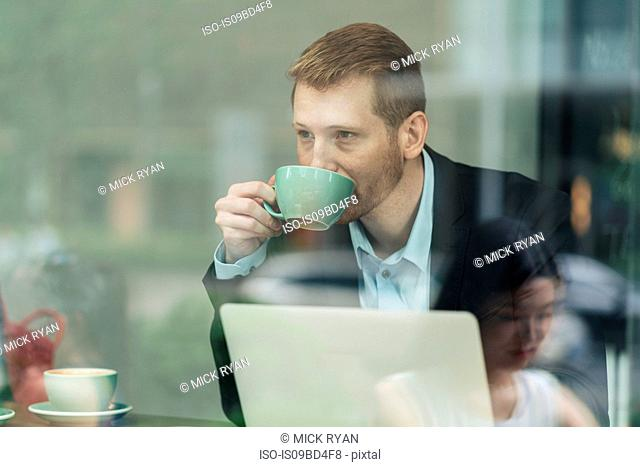 Businessman sitting in cafe, drinking coffee, using laptop, viewed through window
