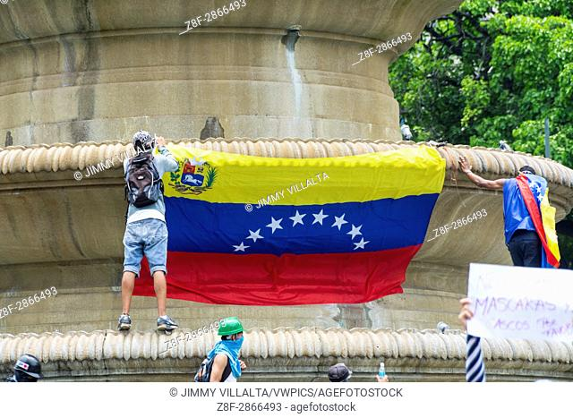 """Young people place a flag of Venezuela in the Obelisk of the France square of Altamira. Under the motto """"""""Our Shield is the Constitution"""""""""""