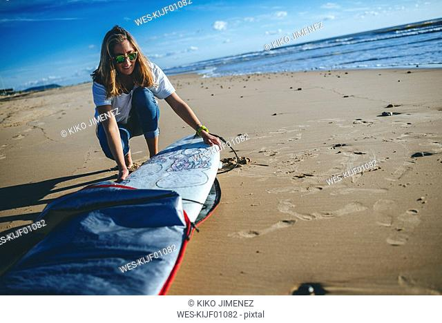 Young woman taking surfboard out of the cover on the beach
