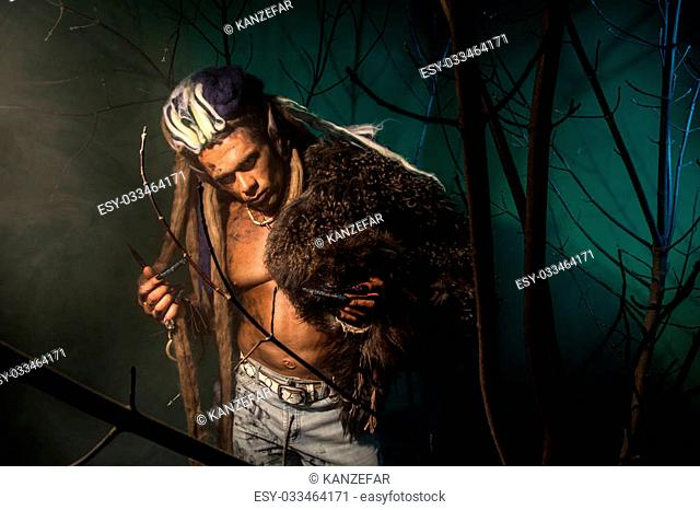 Werewolf with a skin on his skin and long nails among tree branches