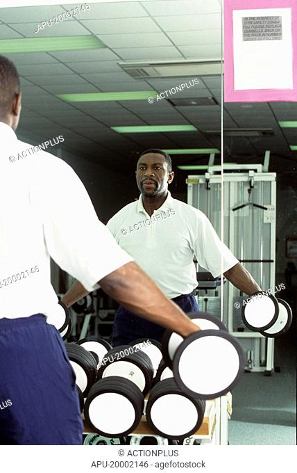 Man working with hand weights by a weight stack in a gym