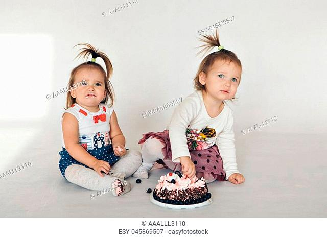 Two little baby girl eating cake isolated white background