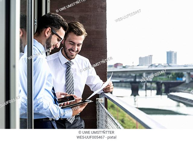 Two young businessmen with documents, smartphone and digital tablet on balcony