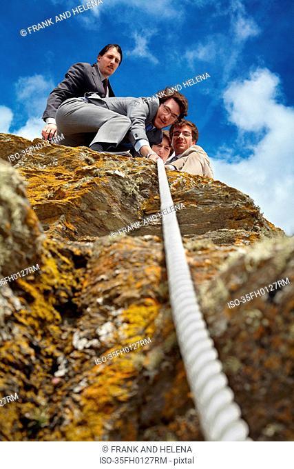 Businessmen pulling rope over cliff