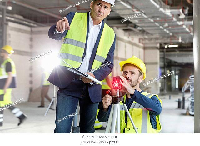 Male foreman and engineer with theodolite at construction site