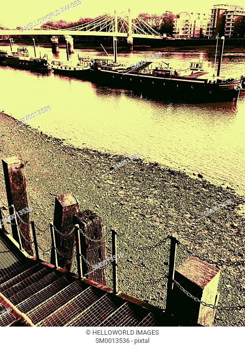 Barges and houseboats on the river Thames by Albert Bridge, London, England