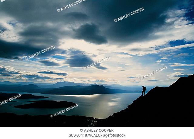 A walker on Ben Mor coigach in the north West Highl,ands of Scotland