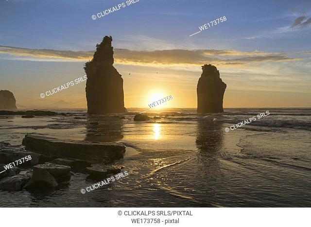 The sun in setting down behind the Three Sisters. Tongaporutu, New Plymouth district. Taranaki region, North Island, New Zealand