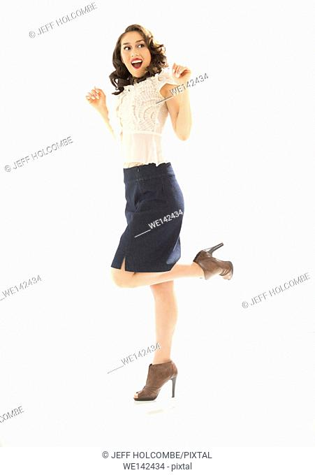 Beautiful young woman in white blouse and blue denim skirt, full length in brown heels, hands up, head turned aside with awesome smile