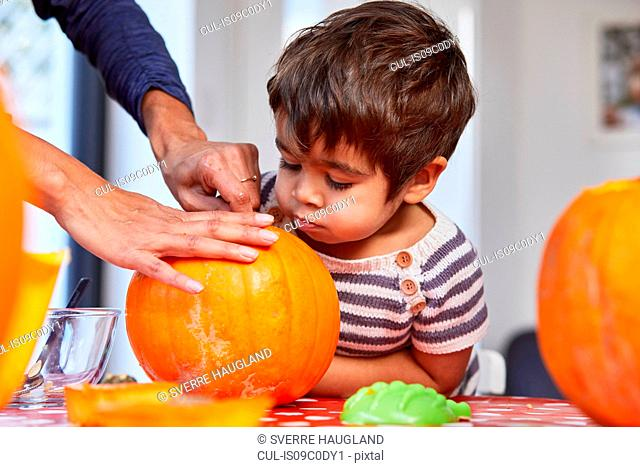 Boy looking at mother gut pumpkin in kitchen
