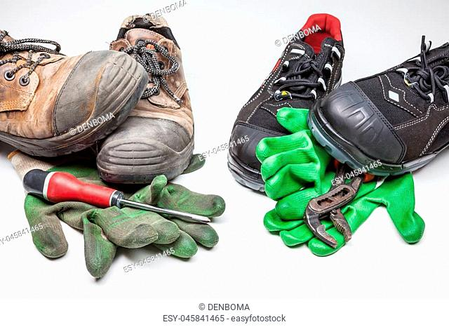 new work shoes and old work shoes with iron tips, new and old work gloves with a cross-screwdriver and a water wrench