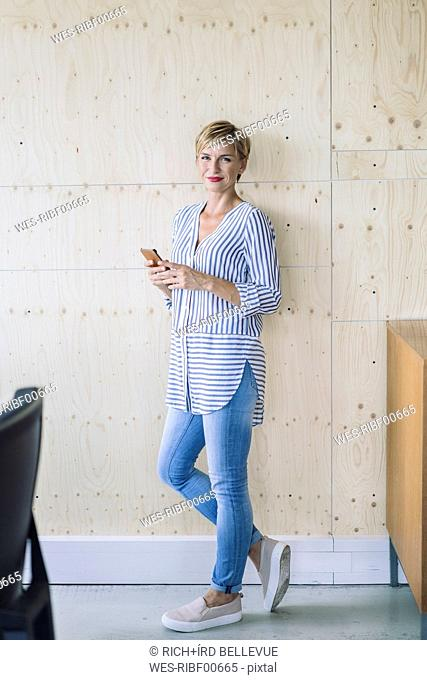 Smiling businesswoman standing at wooden wall in offce