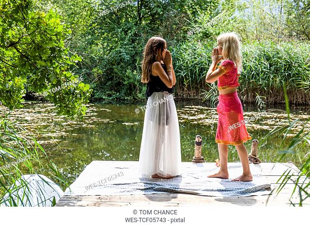 Two girls standing face to face on jetty at a pond in fancy dresses
