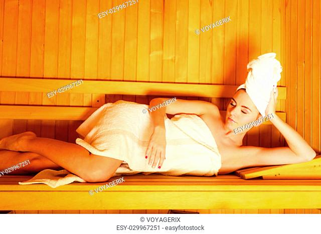 Spa beauty well being and resort concept. Woman in full length white towel lying relaxed in wooden finnish sauna
