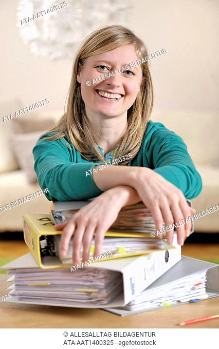 Satisfied woman in front of a big pile of files