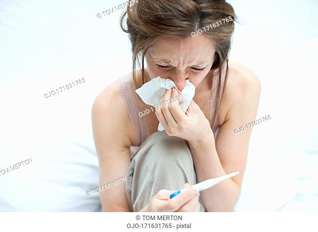 Sick woman taking temperature with digital thermometer and blowing nose