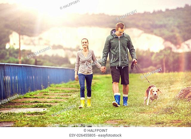 Young couple in colorful wellies walk beagle dog in rain
