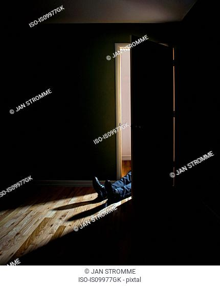 Businessman lying in doorway of dark room
