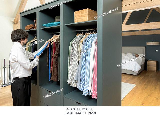Caucasian businessman dressing in bedroom