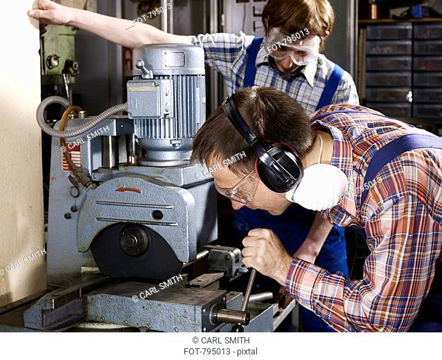 A man using a electric saw in a workshop while a young man looks on