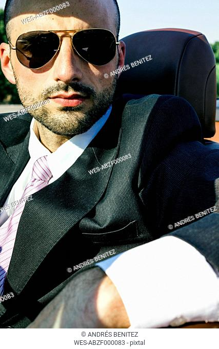 Portrait of businessman with sunglasses in a convertible car