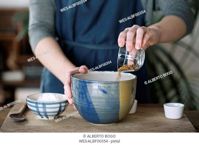 Woman preparing batter for homemade vegan chickpea cookies, partial view