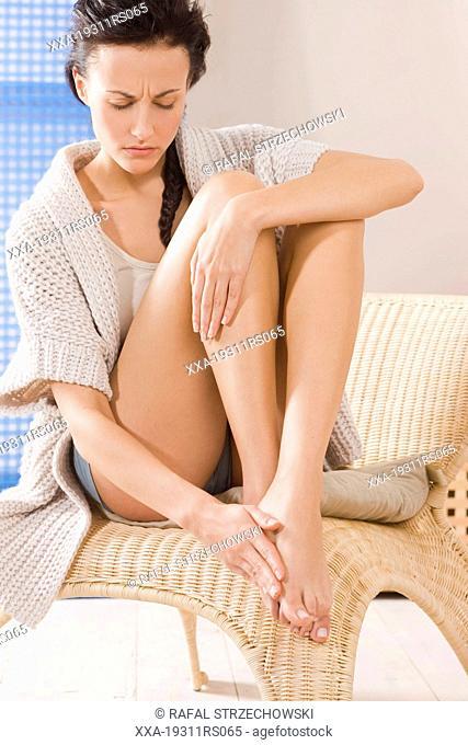 Young woman massaging feet