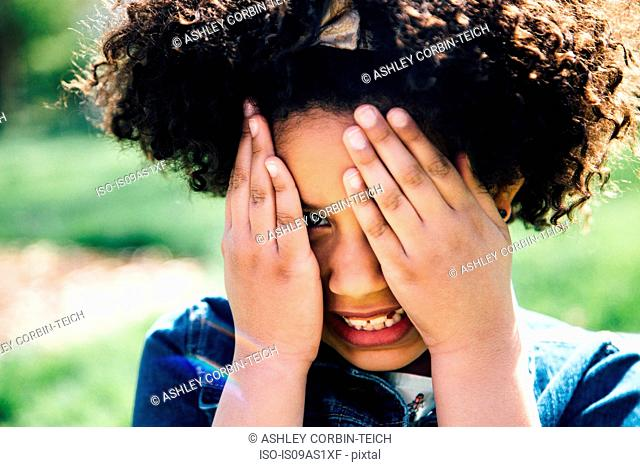 Close up portrait of girl covering face with hands