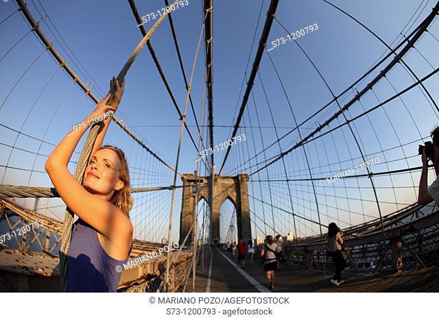 Woman poses at Brooklyn Bridge at sunset, Manhattan, New York, USA