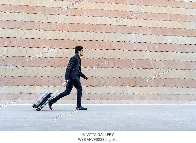 Running young businessman with rolling suitcase