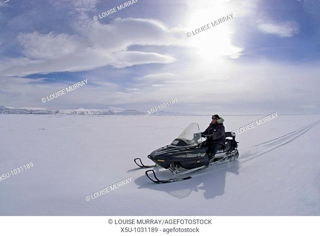 Canadian High Arctic, Lancaster Sound, Nunavut Canada May 2004 Driving snowmobile on sea ice