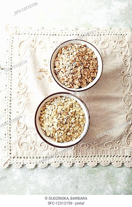 Organic Spelt and Oat Flakes in ceramic bowls