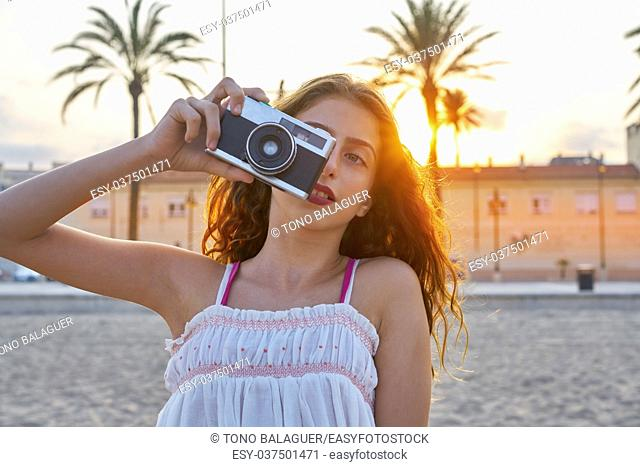Teen girl with retro photo camera at sunset as a photographer
