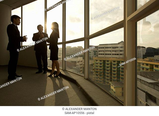 Singapore, Silhouette of three business people discussing ideas in office