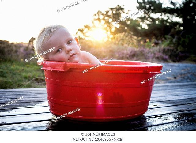 Portrait of cute boy lying in large bowl