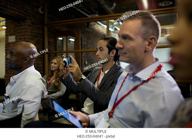 Businessman using camera phone in conference audience
