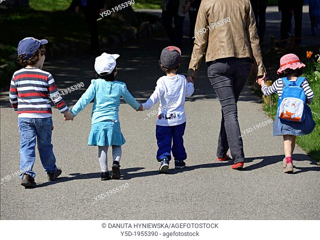 young woman walking hand in hand with four children, Perle du Lac Parc on the shore of Geneva Lake, Geneva, Switzerland