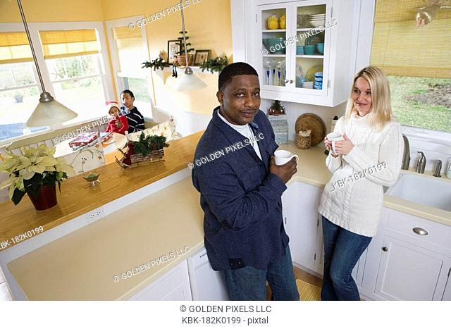 Interracial couple in then kitchen with children in background