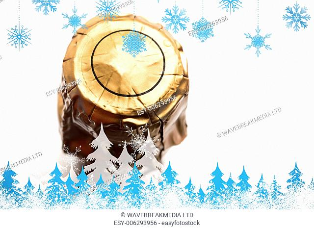 Snowflakes and fir trees against foil on champagne bottle