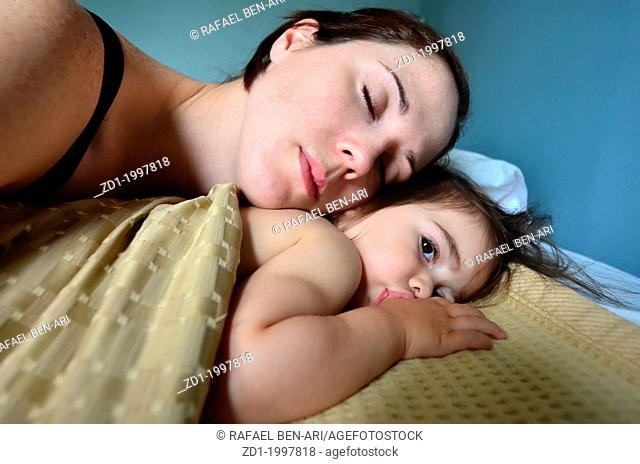 A young mother hugs her baby in bed