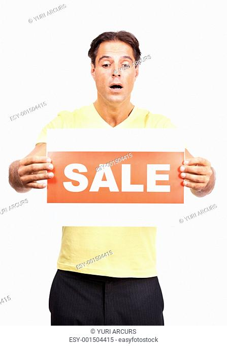 Portrait of a surprised young man holding sale sign isolated against white background
